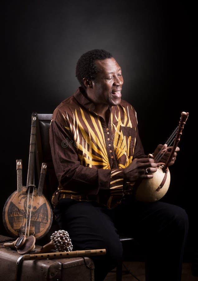 Afrikanischer schwarzer Mann mit ethnischem Musikinstrument stockfotos