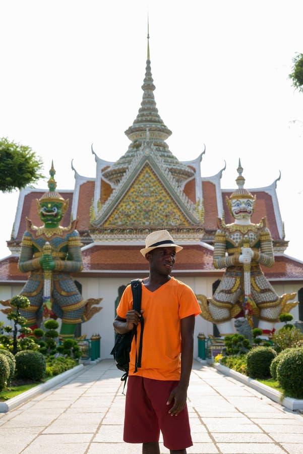 Afrikanischer touristischer Mann, der an Wat Arun Buddhist-Tempel denkt lizenzfreie stockfotos