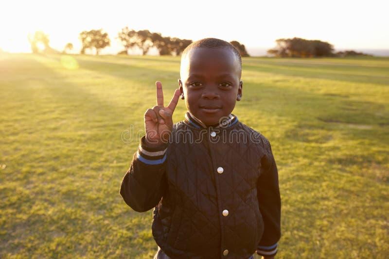 Afrikanischer Volksschulejunge, der Friedenszeichen macht lizenzfreies stockfoto