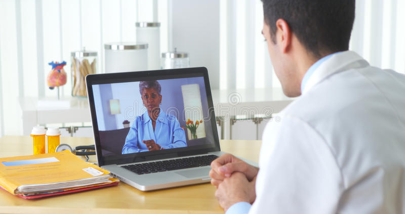 Afrikanisches geduldiges Video, das mit älterem Patienten plaudert stockbilder