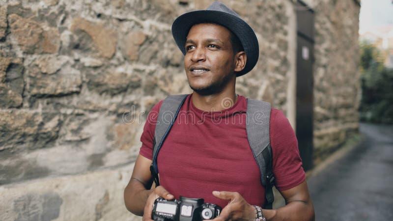 Afrikanisches glückliches touristisches nehmendes Foto auf seiner dslr Kamera Junger Mann, der in Europa reist lizenzfreies stockbild