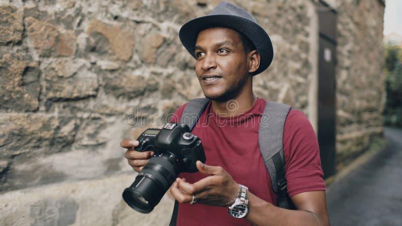 Afrikanisches glückliches touristisches nehmendes Foto auf seiner dslr Kamera Junger Mann, der in Europa reist stockfotos