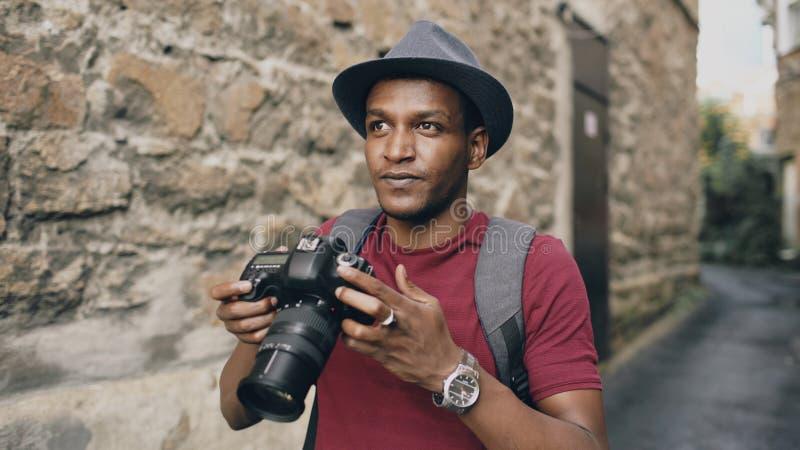 Afrikanisches glückliches touristisches nehmendes Foto auf seiner dslr Kamera Junger Mann, der in Europa reist lizenzfreie stockfotografie