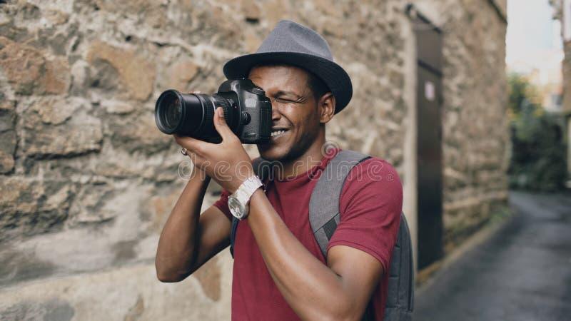 Afrikanisches glückliches touristisches nehmendes Foto auf seiner dslr Kamera Junger Mann, der in Europa reist stockbilder
