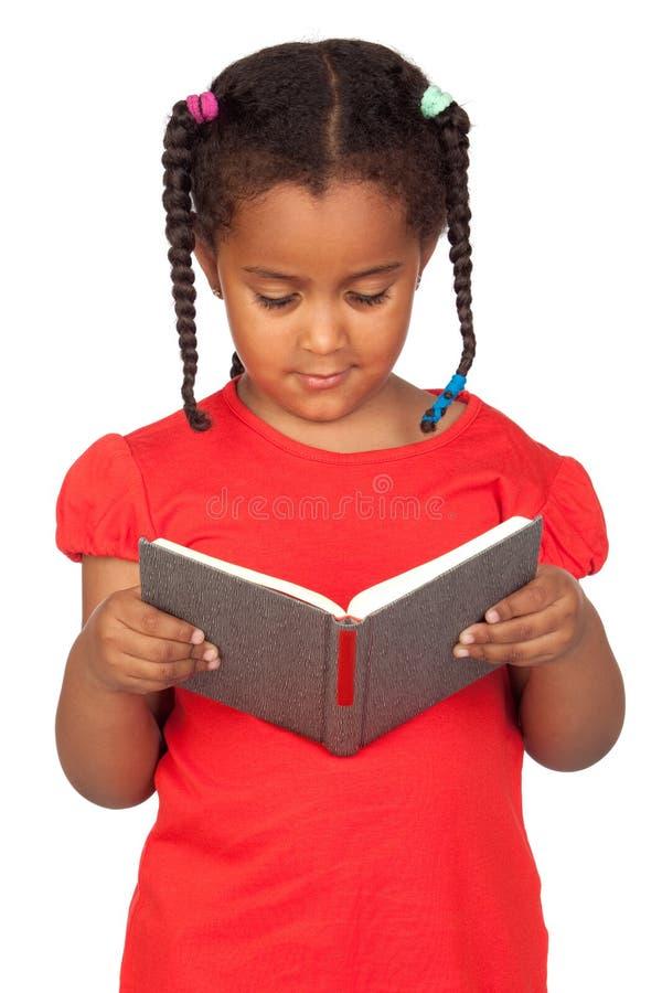 Afrikanisches kleines Mädchen, das ein Buch liest stockfoto