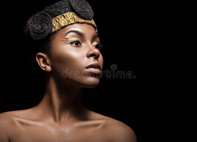 Afrikanisches Mädchen mit hellem Make-up und kreatives Goldzubehör auf dem Kopf Schönes lächelndes Mädchen stockfotografie