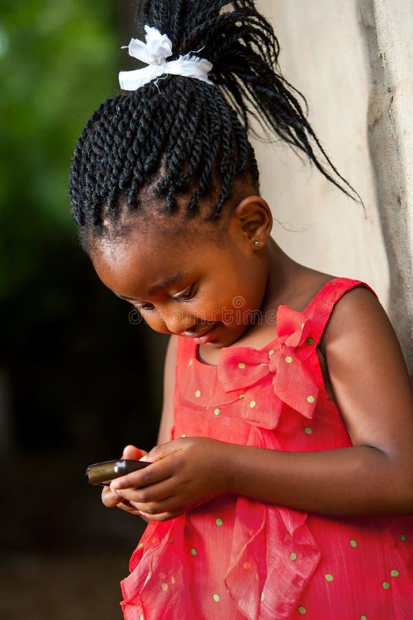 Afrikanisches Mädchen Pigtailed, das mit intelligentem Telefon spielt. stockfoto
