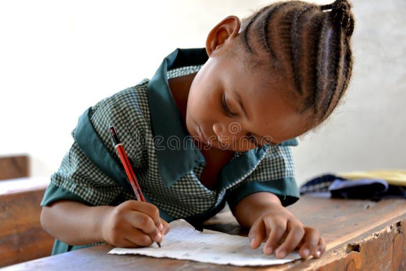 Afrikanisches Schulmädchen-Schreiben lizenzfreie stockbilder