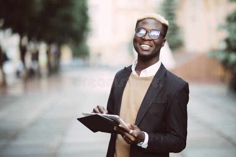 Afrikansk affärsman som arbetar med den utomhus- minnestavlan Svarta människor - begrepp om folk, affär, livsstil och teknologi arkivbild