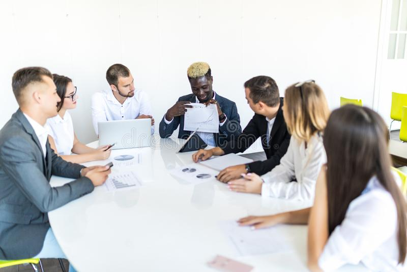 Afrikansk affärsman som förklarar försäljningsgrafen till kollegor, i möte Projekt summ royaltyfria bilder