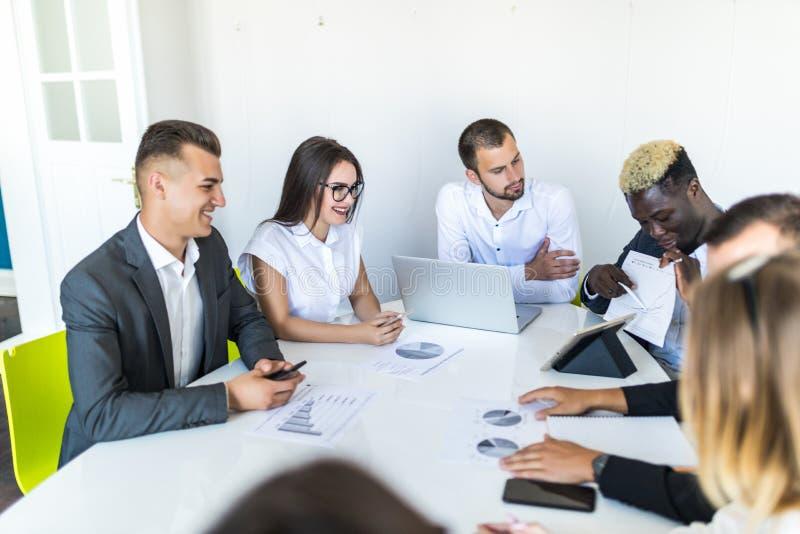 Afrikansk affärsman som förklarar försäljningsgrafen till kollegor, i möte Projekt summ fotografering för bildbyråer