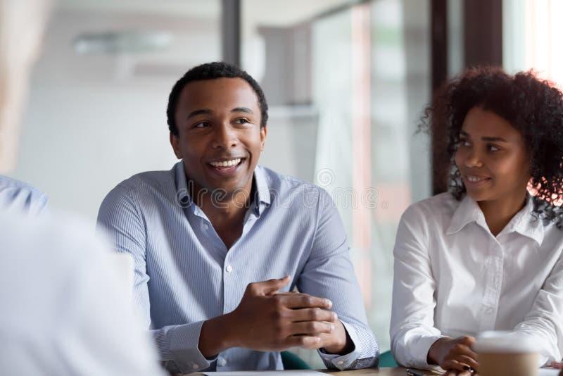 Afrikansk affärsmanlagledare som talar till kollegor på gruppmötet royaltyfria foton