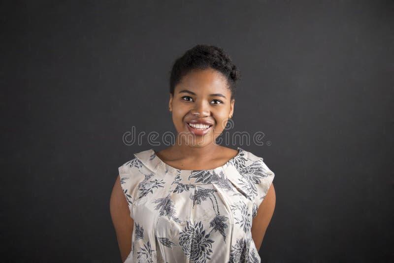 Afrikansk amerikan kvinna med armar bak baksida på svart tavlabakgrund arkivfoton