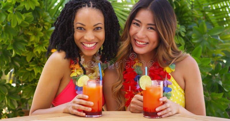 Afrikansk amerikan- och japanbästa vän som tillsammans tycker om tropisk semester fotografering för bildbyråer