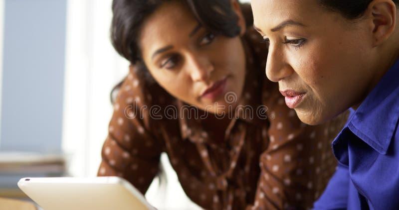 Afrikansk amerikan- och latinamerikanaffärskvinnor som använder minnestavladatoren royaltyfri bild