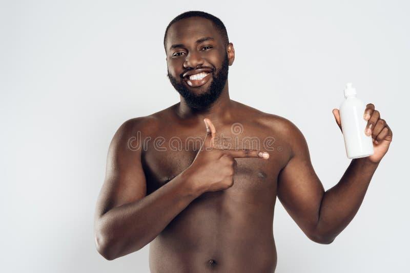 Afrikansk amerikan som ler hållande aftershave för man royaltyfria bilder