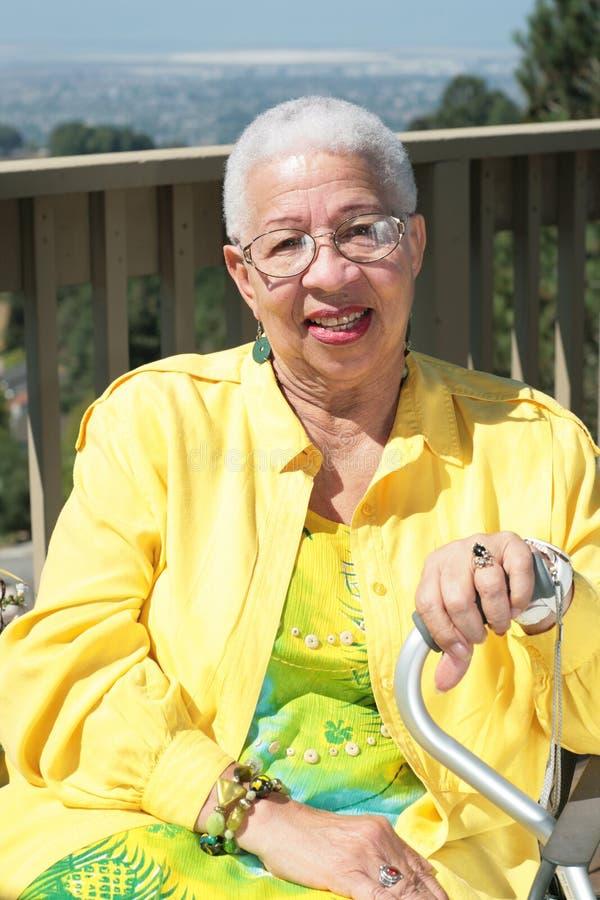 afrikansk amerikan som sitter utomhus den le kvinnan royaltyfri fotografi