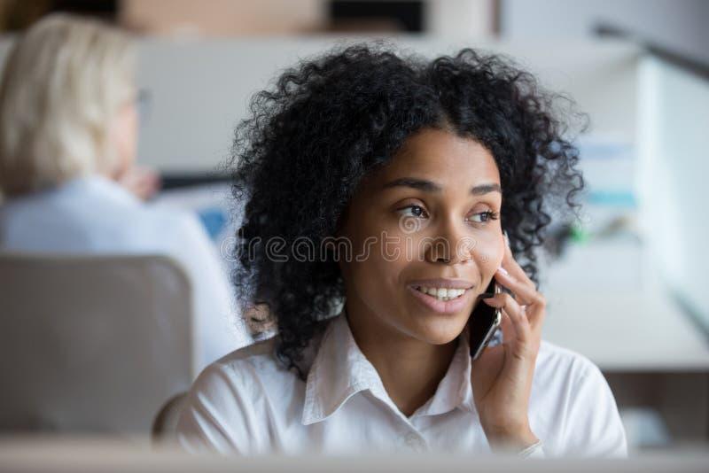 Afrikansk amerikanaffärskvinna som talar på telefonen på arbetsplatsen royaltyfria bilder