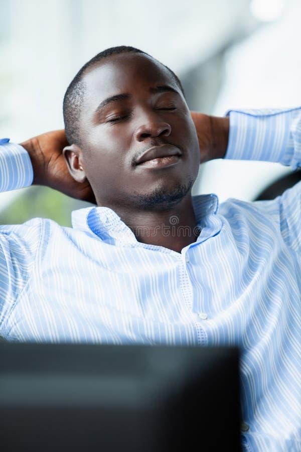 Afrikansk amerikanaffärsman i blå skjorta som i regeringsställning kopplar av efter hård arbetsdags arkivbild