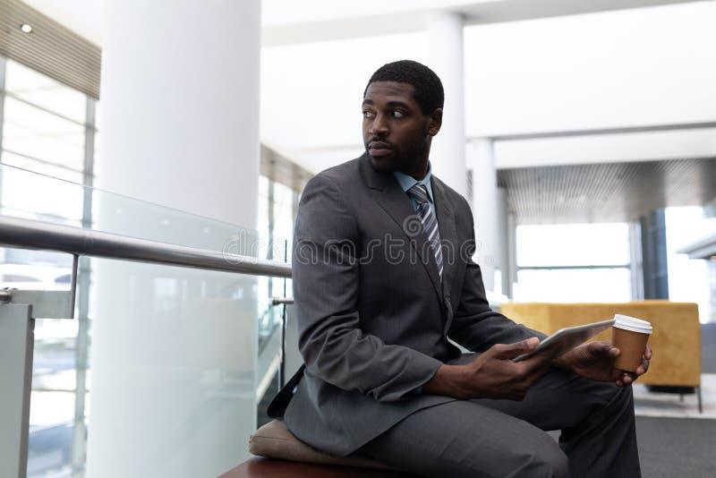 Afrikansk amerikanaffärsman med kaffekoppen och den digitala minnestavlan som bort i regeringsställning ser royaltyfri bild