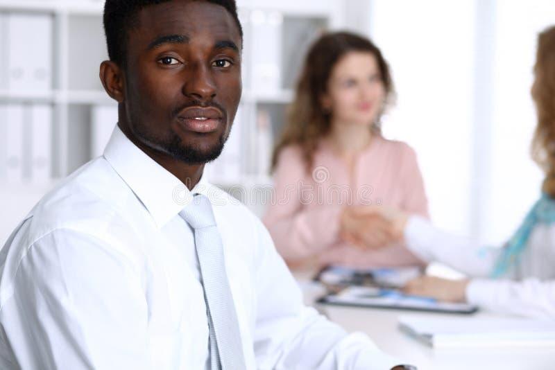 Afrikansk amerikanaffärsman på möte i regeringsställning, färgat i vit Mång- etnisk grupp för affärsfolk arkivbild
