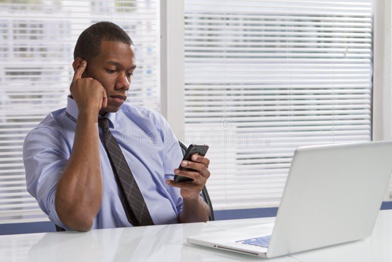 Afrikansk amerikanaffärsman på skrivbordet genom att använda smartphonen som är horisontal royaltyfri bild