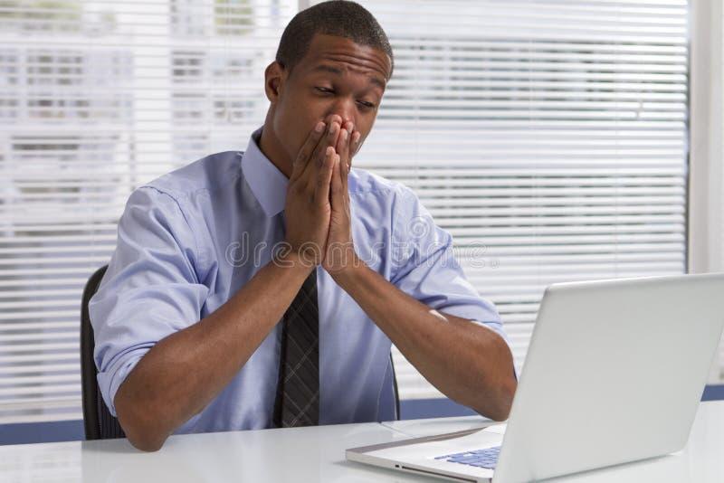 Afrikansk amerikanaffärsman på skrivbordet med datoren som är horisontal royaltyfria bilder