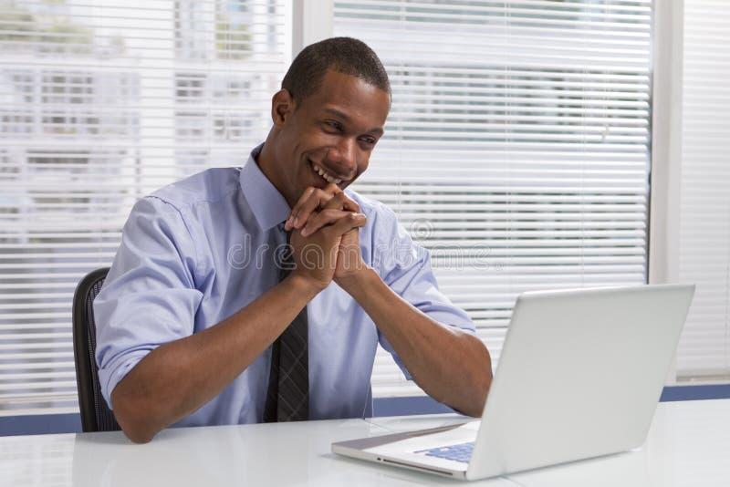 Afrikansk amerikanaffärsman på skrivbordet med datoren som är horisontal royaltyfri foto