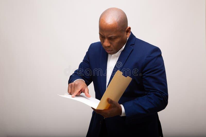 Afrikansk amerikanaffärsman Points To Page i mapp royaltyfri foto