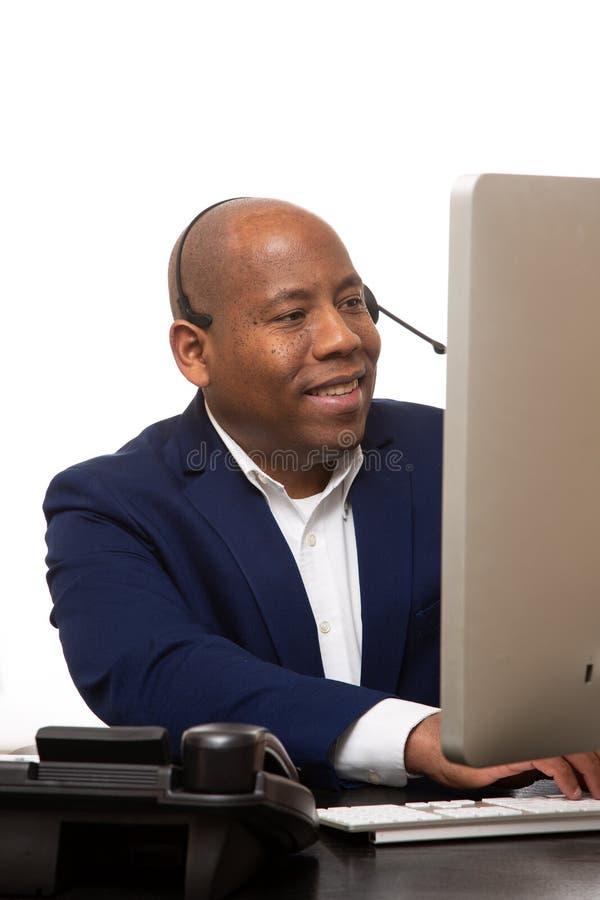 Afrikansk amerikanaffärsman Sitting In Front av datoren royaltyfri bild