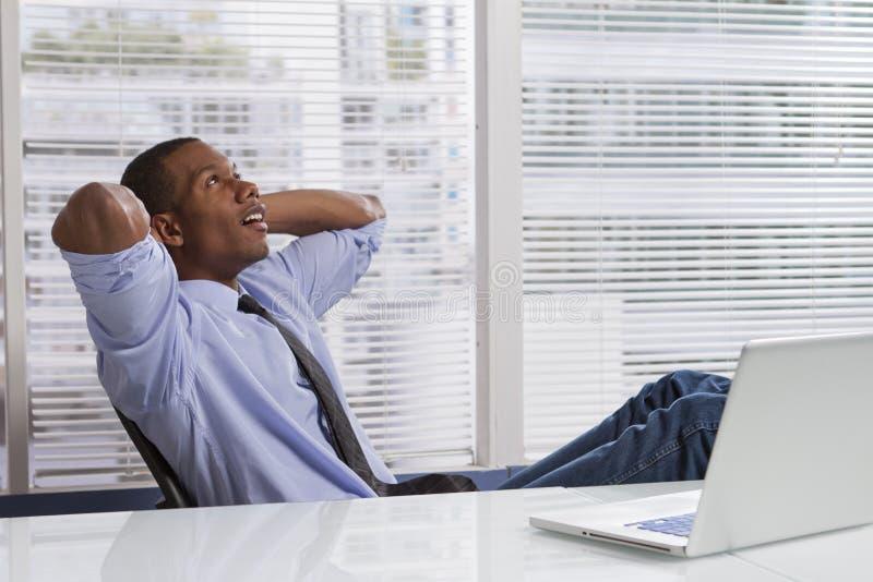 Afrikansk amerikanaffärsman som kopplar av på skrivbordet som är horisontal royaltyfria foton