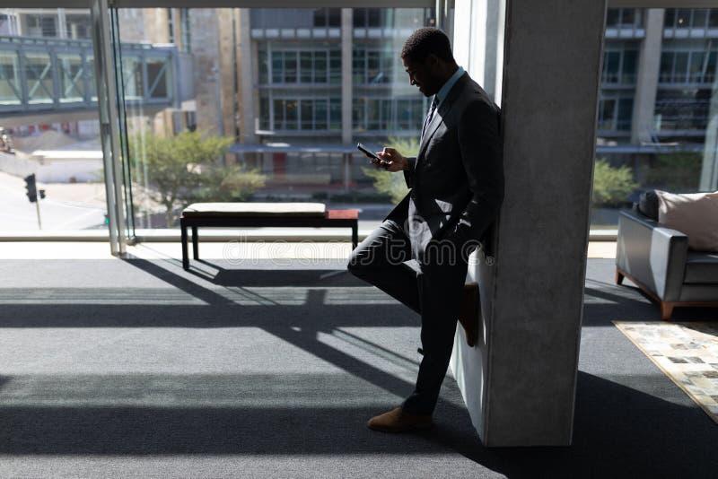 Afrikansk amerikanaffärsman som lutar mot väggen och i regeringsställning använder mobiltelefonen royaltyfri foto