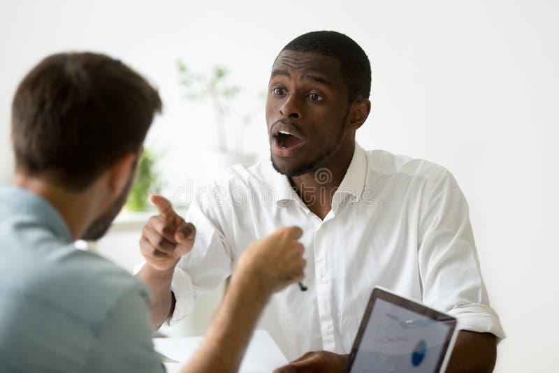 Afrikansk amerikanaffärsman som ogillar att debattera under negotia royaltyfria foton