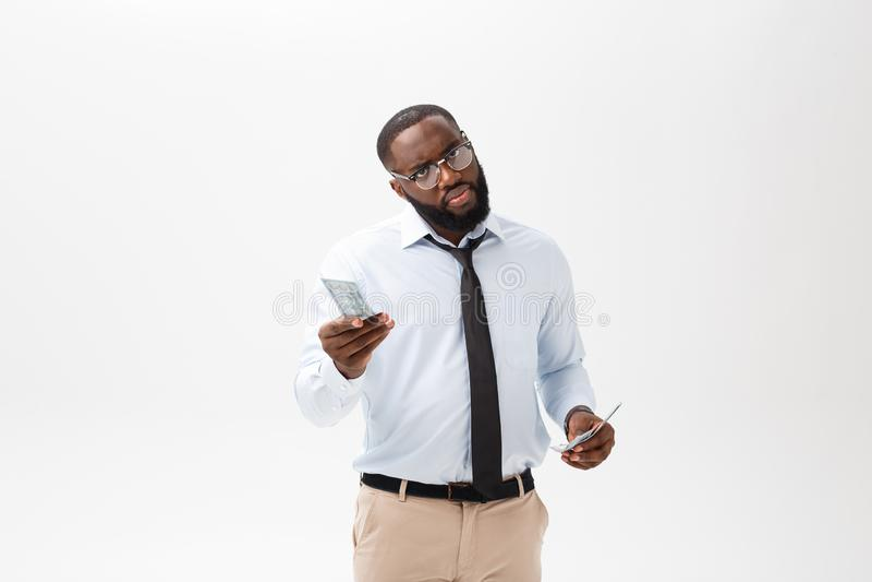 Afrikansk amerikanaffärsman som rymmer kassa och den allvarliga seende kameran Inomhus isolerat på grå bakgrund royaltyfri foto