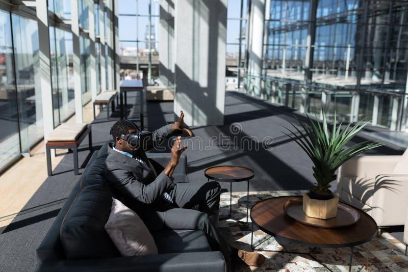 Afrikansk amerikanaffärsman som sitter på soffan och i regeringsställning använder virtuell verklighethörlurar med mikrofon fotografering för bildbyråer