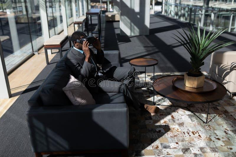 Afrikansk amerikanaffärsman som sitter på soffan och i regeringsställning använder virtuell verklighethörlurar med mikrofon royaltyfria bilder