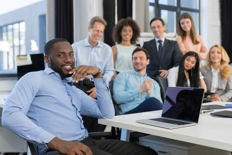 Afrikansk amerikanaffärsmanLeading Meeting In idérikt kontor, framstickande Using Laptop Computer i förgrund över affär arkivfoto
