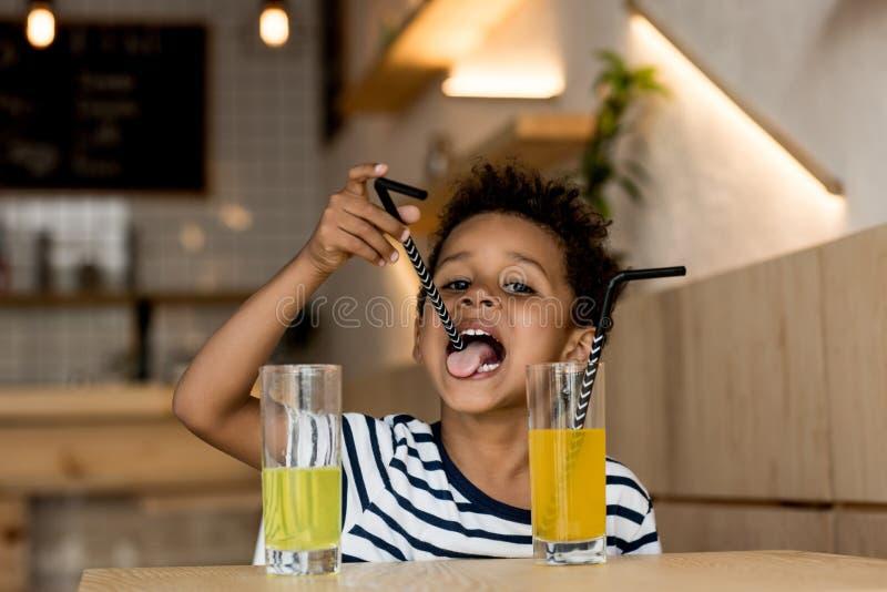 Afrikansk amerikanbarn som dricker fruktsaft arkivfoto