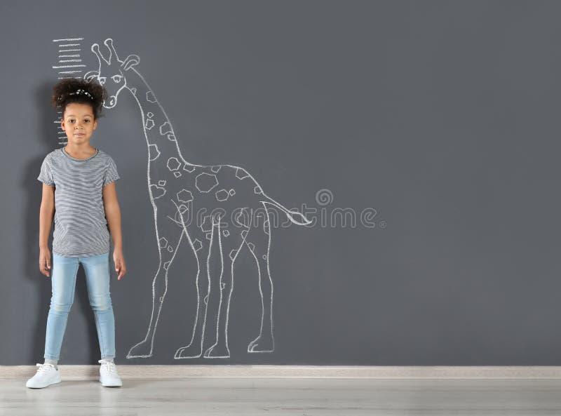 Afrikansk amerikanbarn som mäter höjd nära kritagiraffteckning på den gråa väggen arkivbilder