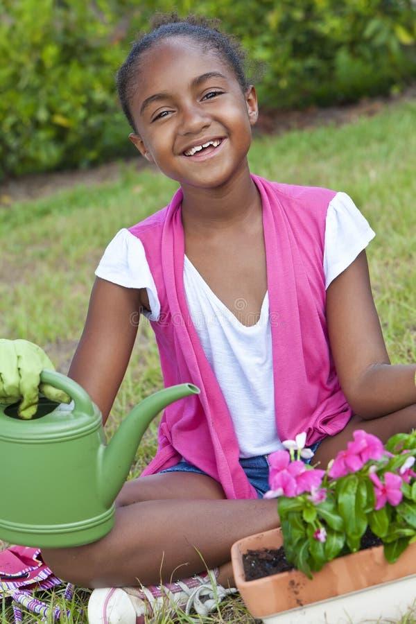 afrikansk amerikanbarnblommor som arbeta i trädgården flickan royaltyfria foton