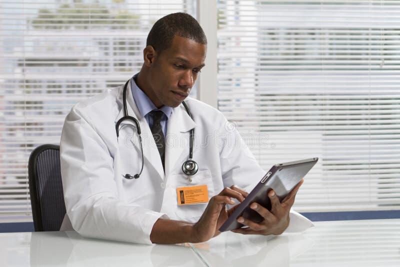 Afrikansk amerikandoktor som använder den elektroniska minnestavlan som är horisontal royaltyfri foto