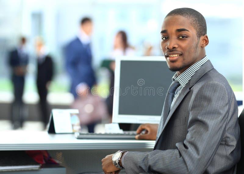 Afrikansk amerikanentreprenör som i regeringsställning visar datorbärbara datorn royaltyfri foto
