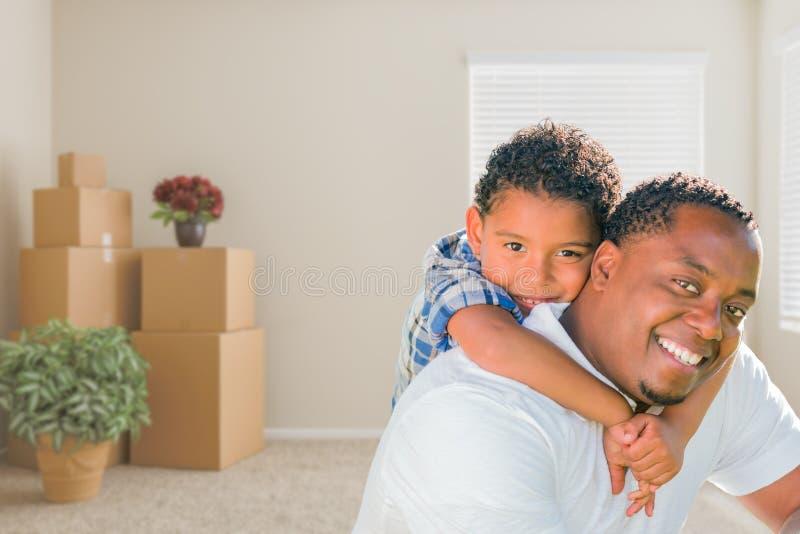 Afrikansk amerikanfader och son för blandat lopp i rum med packat M royaltyfri foto