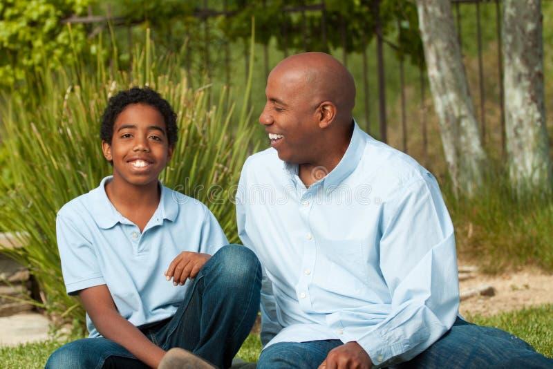 Afrikansk amerikanfader och son som talar och skrattar royaltyfri bild