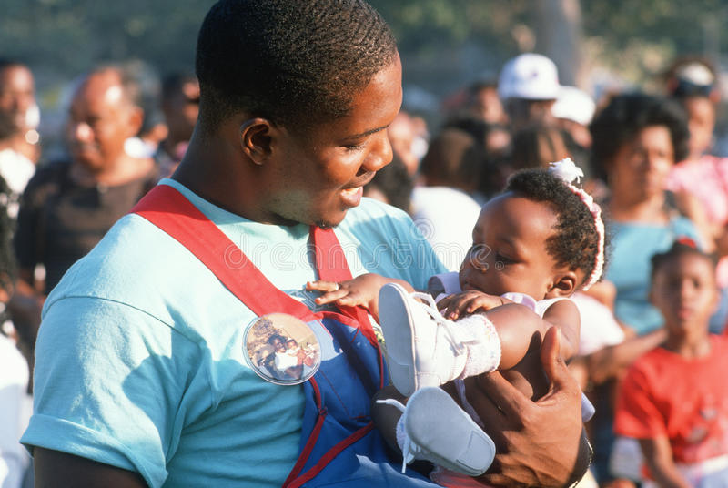Afrikansk amerikanfaderholdingen behandla som ett barn royaltyfria foton