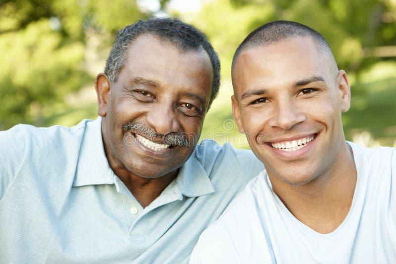 Afrikansk amerikanfadern And Adult Son som in kopplar av, parkerar royaltyfri foto