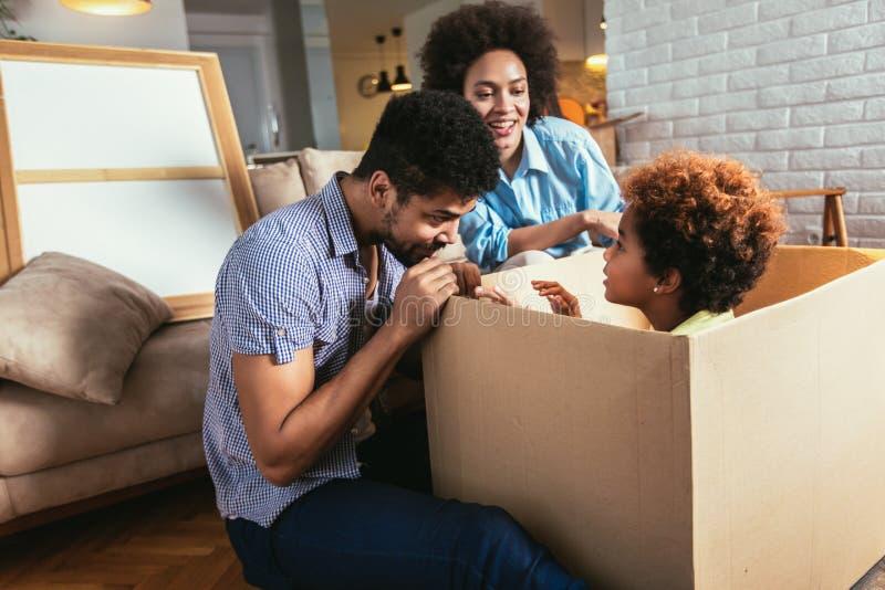 Afrikansk amerikanfamilj, föräldrar och dotter som packar upp askar och flyttar sig in i ett nytt hem arkivfoto