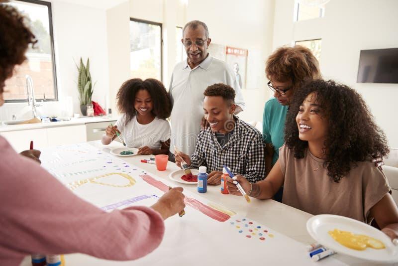 Afrikansk amerikanfamilj för tre utveckling i köket som tillsammans gör ett tecken för ett överraskningparti, slut upp fotografering för bildbyråer