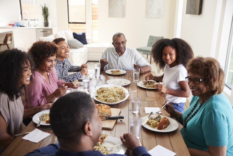 Afrikansk amerikanfamilj för tre utveckling som sitter på tabellen som tillsammans talar och äter matställen, slut upp royaltyfri foto