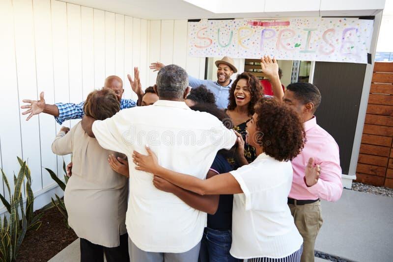 Afrikansk amerikanfamilj för tre utveckling som välkomnar morföräldrar till ett överraskningparti arkivfoton